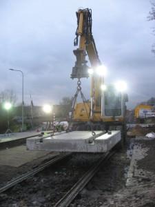 Foto: de eerste raildraagplaat voor de overweg in spoor 101 hangt klaar in de kraan.